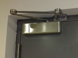 commercial stainless steel door closer in close up view