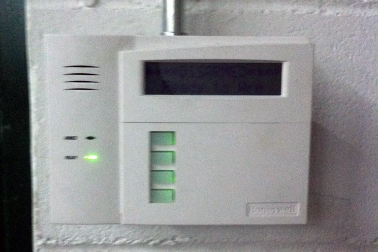 Honeywell Alarm System touch pad on a warehouse wall