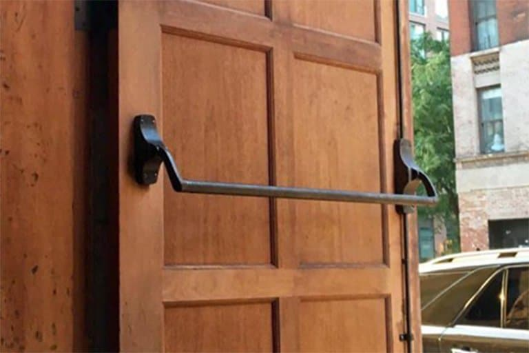 Close up view of wooden door with exit device installed