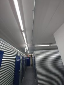 View of metal pipes containing new wiring running along the ceiling making a right angle down a hallway
