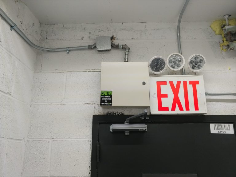 Wall mounted DVR locked box next to lighted exit sign above a door frame