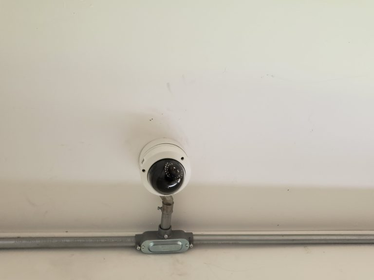 IP camera installed on a ceiling with piping visible