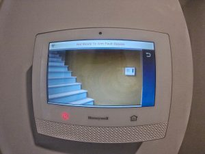 View of Honeywell residential security alarm panel with stairway view on the screen