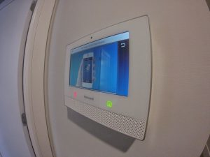 Side view of View of Honeywell residential security alarm panel with a hand and cell phone on the screen