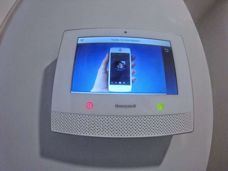 Front view of View of Honeywell residential security alarm panel with a hand holding a cell phone on the screen