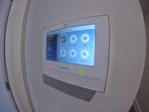 Honeywell control pad for a wireless alarm system shown installed on an interior wall from a side view