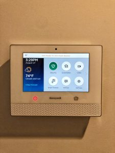 Honeywell control pad for a wireless alarm system shown installed on an interior wall