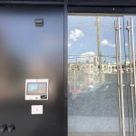 """Front view of ButterflyMX 12"""" touch screen entry panel installed to the left of an exterior door"""