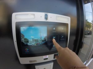 """ButterflyMX 12"""" touch screen entry panel installed with a finger pressing the screen"""