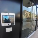 "ButterflyMX 12"" touch screen entry panel shown installed to the left of an exterior door"