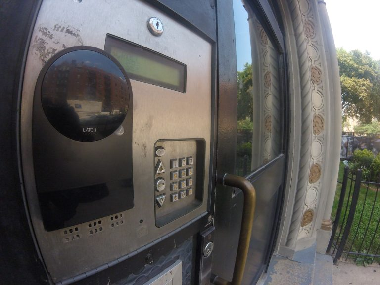 Side view of Latch R installed on an access control panel to the left of an exterior door
