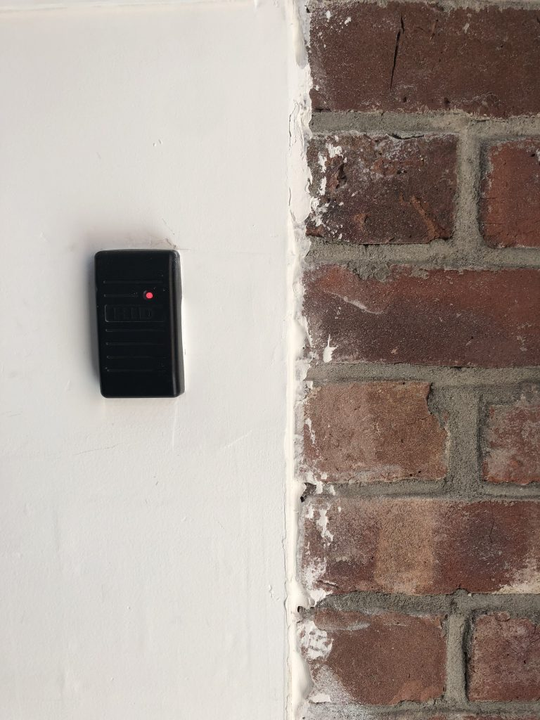 Card reader installed to the left of a brick wall