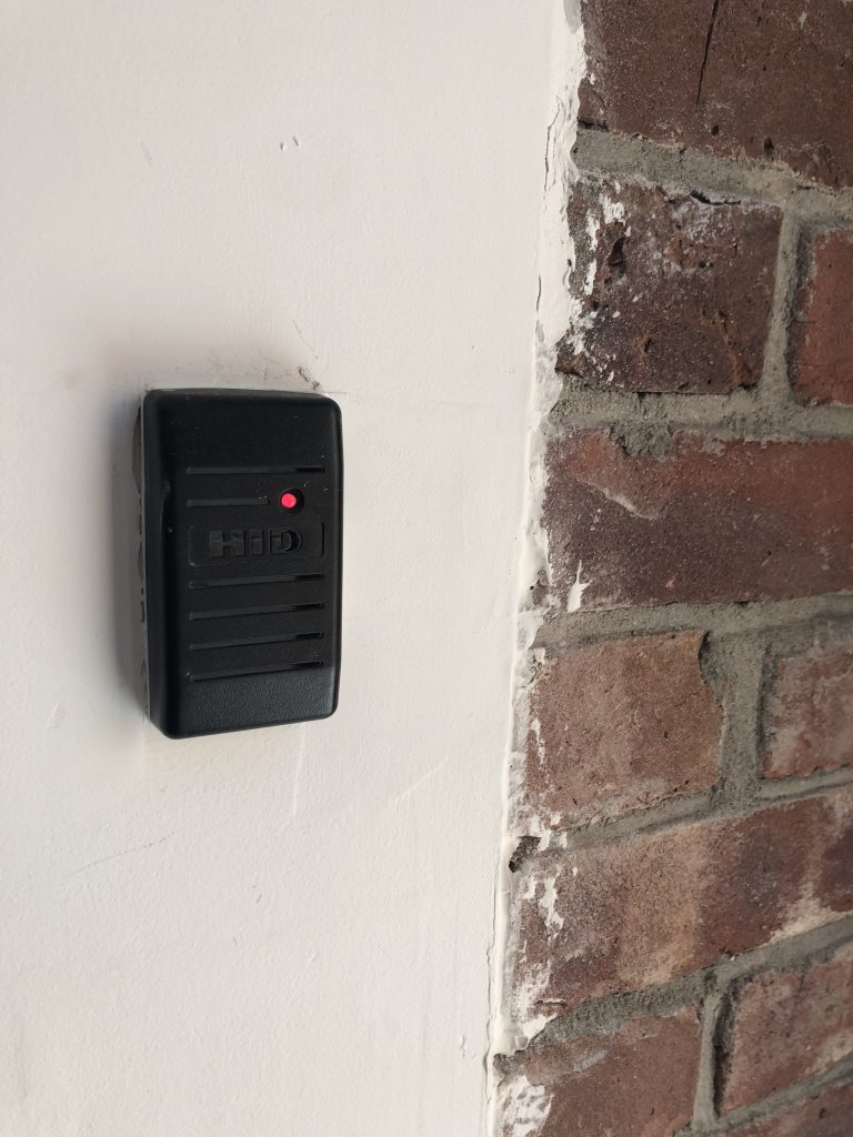 Close up of a Card reader installed to the left of a brick wall