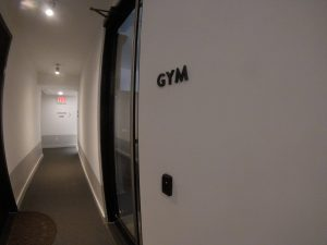 Card reader installed to the right of an interior door under a sign that says GYM