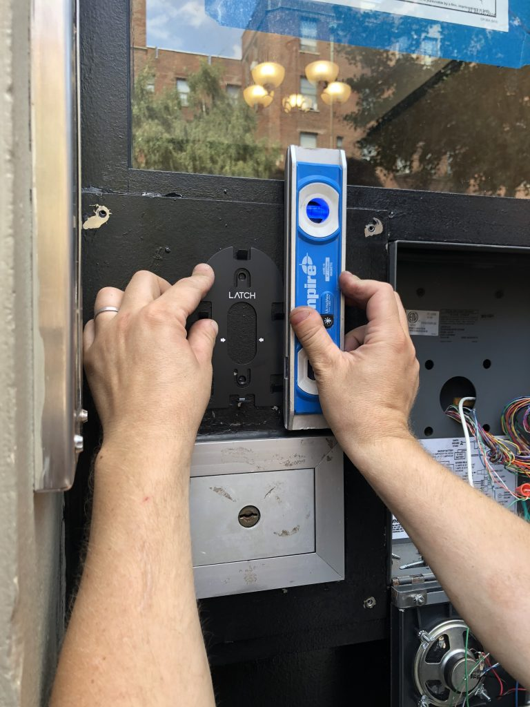 View of an installer with a level completing the install of a Latch R reader