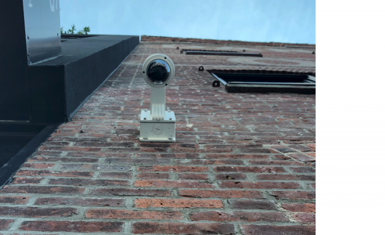 Security camera installed on an exterior brick wall shown from below