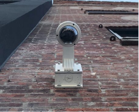 Security camera installed on an exterior brick wall shown from below and close up