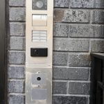 Close up view of ABB video intercom panel installed on an exterior brick wall