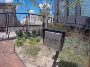 Panel to open exterior gate with sign that says Push To Open