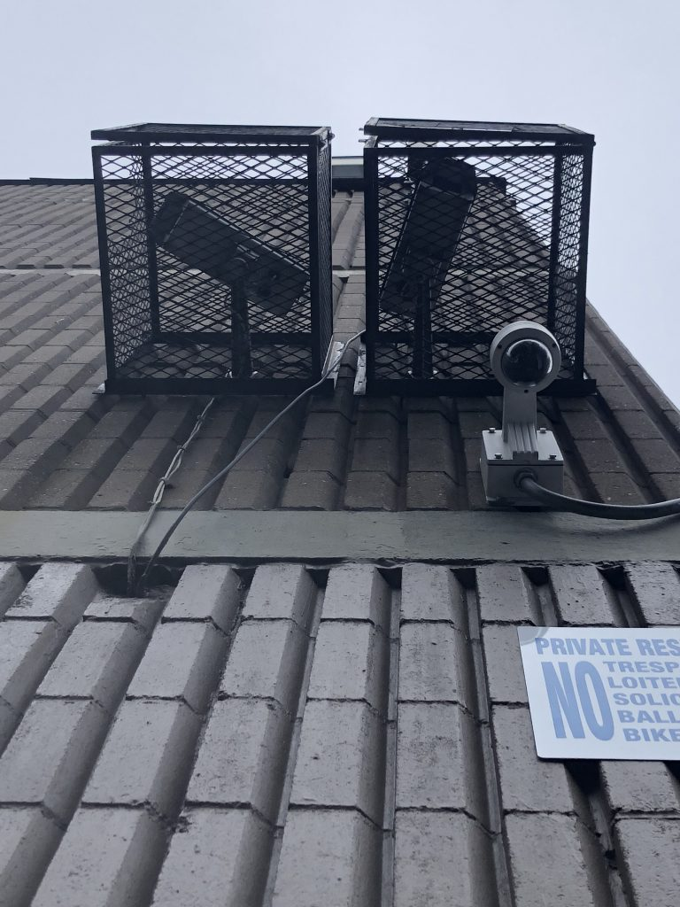 Security Camera installed seen from below with 2 metal utility cages