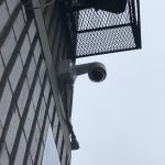 Security Camera installed seen from the side with a metal utility cage