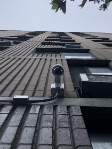 Security Camera installed seen from below on a tall exterior wall