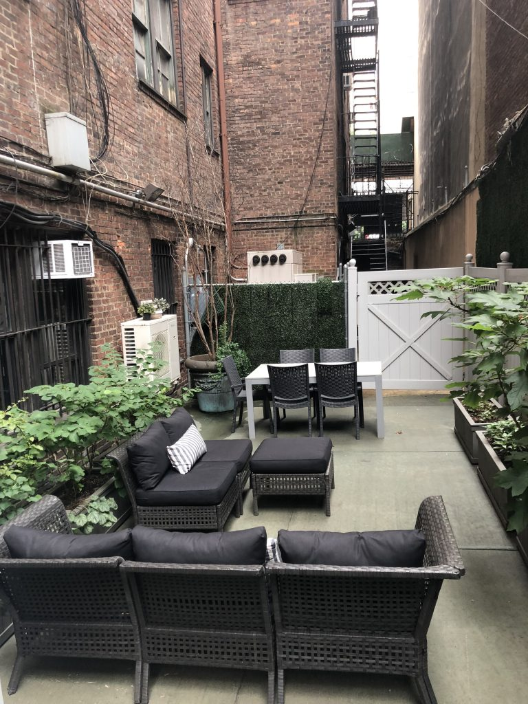 Outdoor patio with seating area and utility boxes in the background