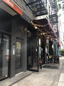 View of door with intercom system next door to a bar/restaurant