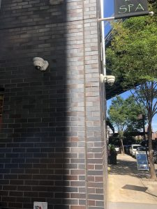 2 IP Cameras installed on either side of the corner of a brick building