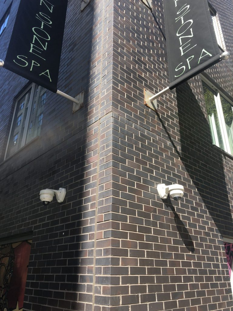 Close up of 2 IP Cameras installed on either side of the corner of a brick building