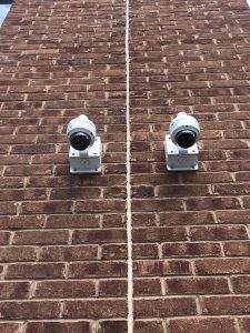 2 security cameras installed side by side on an exterior brick wall.