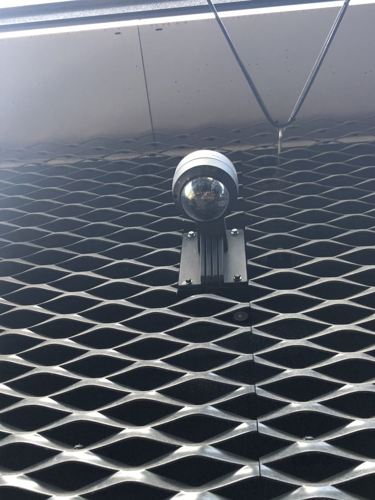 Exterior dome camera shown installed on a metal grate