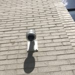 Exterior dome security camera show installed from below on a brick wall