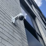 Exterior dome security camera show installed from below and side on a brick wall