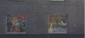 2 murals embedded in a brick wall